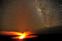 Long exposure showing the Milky Way stars above Halema'uma'u crater with red hot lava burning from the cauldron, Hawai'i Volcanoes National Park, Big Island.