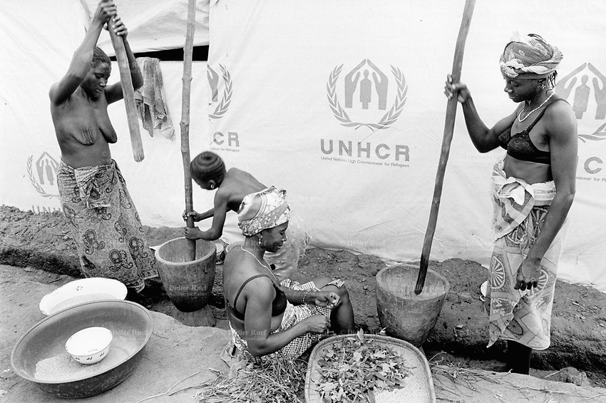 "Guinea. State of ""Guinée Forestière"". Katkama. Women grind cereals to prepare the daily meal. UNHCR (United Nations High Commision for the refugees) transit camp for Sierra Leoneans  refugees. UNHCR's decision is to carry out the refugee evacuation movement out of the troubled camps of the ""Parrot's beak"" region for a relocation in safer camps. Daily life outside a tent where up to 20 families with families and children share the same tent and space.   © 2001 Didier Ruef"
