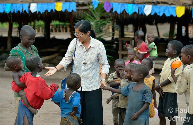 Sister Rosa Le Thi Bong, a Vietnamese member of Sisters of Our Lady of the Missions, talks with children in the Makpandu refugee camp, a ramshackle collection of huts with mud walls and thatched roofs spread through a remote section of forest 40 kilometers from Yambio, the capital of Western Equatoria State in the newly independent South Sudan. More than 3,000 people live in the camp, having fled the Democratic Republic of the Congo in 2008 when the Lord's Resistance Army started a murderous rampage through the area. In recent months the Congolese have been experiencing harassment and insults from the local population. Religious workers say the refugees want to go home to the Congo, but not until Joseph Kony and the LRA are removed. Sister Rosa works in the camp as a member of Solidarity with South Sudan, a pastoral and teaching presence of Catholic priests, sisters and brothers from around the world.