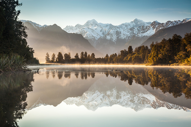Misty Sunrise and perfect reflections of Mt Cook, Mt Tasman & Southern Alps at Lake Matheson, West Coast NZ. Westland Tai Poutini National Park NZ.