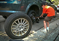 Young boy changes flat tire.