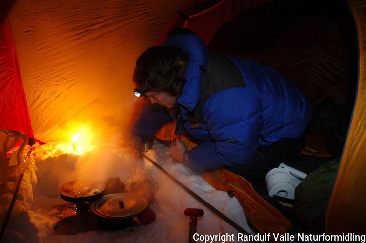 Mann lager mat i teltet ---- Man cooking inside tent