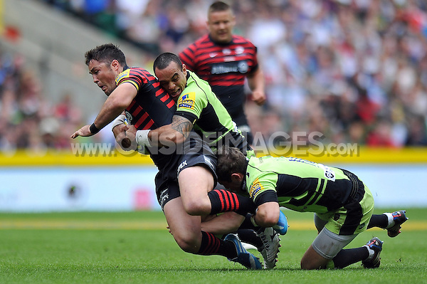 Brad Barritt is double-tackled to ground. Aviva Premiership Final, between Saracens and Northampton Saints on May 31, 2014 at Twickenham Stadium in London, England. Photo by: Patrick Khachfe / JMP