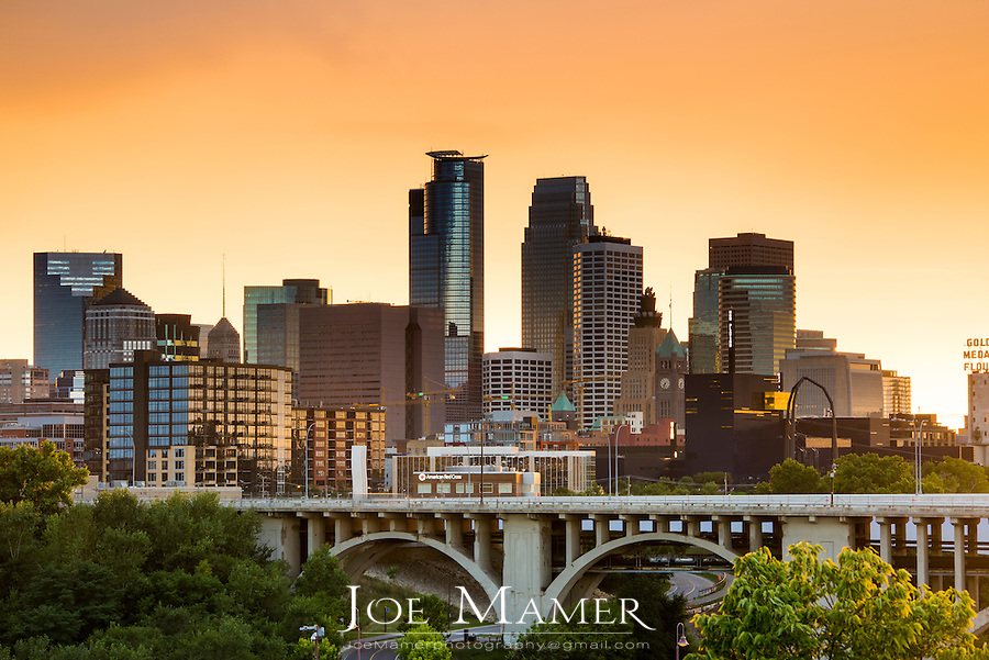 Minneapolis skyline and Tenth Avenue bridge with orange storm light.