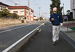Volunteer Ryuji Yokoyama, 49, takes radiation readings on the deserted streets of Minami-Soma, Fukushima Prefecture, Japan on 30 March, 2011. Despite being inside the 30 km exclusion zone, Yokoyama is among around 10,000 residents who either cannot or don't want to leave their homes.  Photographer: Robert Gilhooly