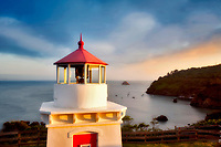 Trinidad Lighthouse with boats in harbor and sunset. California