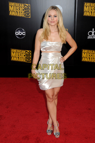 KRISTEN BELL. 2009 American Music Awards - Arrivals held at the Nokia Theatre L.A. Live, Los Angeles, California, USA..November 22nd, 2009.AMA AMA's full length silver white strapless wrap dress silk satin hand on hip clutch bag.CAP/ADM/BP.©Byron Purvis/AdMedia/Capital Pictures.