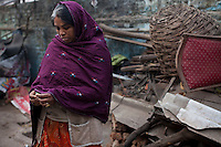 Urmila Maurya, 38, stands amidst the pile of rubble which was once her home in the institutional area of Lodi Colony, an upmarket area in New Delhi, India on 03 January 2012. A mother of 2, she spends her days on the pavement stringing flowers into garlands for devotees at the nearby Hindu temple. At night, she lays down on the same plastic tarpaulin she uses for the flowers but claims that the police come and tear it up in an attempt to discourage her from squatting in the open. Photo by Suzanne Lee for The National