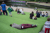 Young man sleeping on astroturf lanscaping by the Grand Union canal, Kings Cross, London.