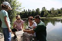 Vorsitzender Andreas Krüger vom ASV Rotauge kontrolliert die Reuse, Ilonka Ludwig, Laura (l.) und Daniela Schätzke (2vl) sehen zu