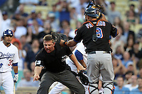 Umpire Greg Gibson points to where the base runner touched home plate while New York Mets catcher Ronny Paulino #9 disagrees during game against the Los Angeles Dodgers at Dodger Stadium on July 7, 2011 in Los Angeles,California. (Larry Goren/Four Seam Images)