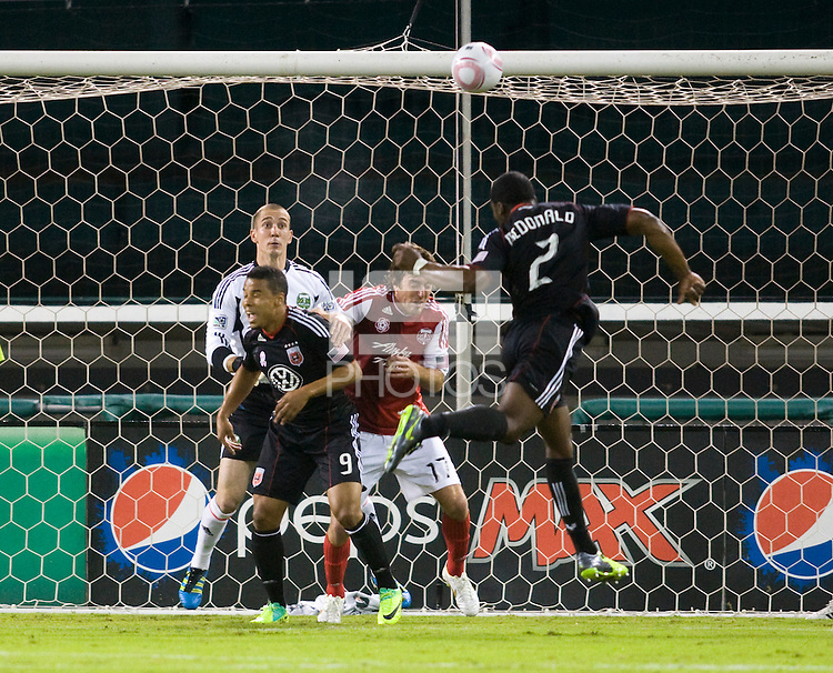 Brandon McDonald (2) of D.C. United heads a ball onto the crossbar as Troy Perkins (1) of the Portland Timbers watches during the game at RFK Stadium in Washington, D.C. D.C. United tied the Portland Timbers, 1-1.