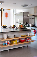 Two large wooden shelves built in to the central kitchen island are a practical and functional storage solution for everyday crockery