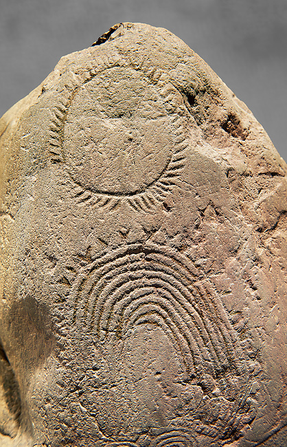 """Prehistoric  petroglyphs, rock carvings, of geometric designs carved by the the prehistoric Camuni people in the Copper Age around the 3rd milleneum BC, Stele """"Bagnolo 2"""" found in 1972 from Malegno near Bangnolo Ceresolo. Museo Nazionale della Preistoria della Valle Camonica ( National Museum of Prehistory in Valle Cominca ), Lombardy, Italy. Grey Art Background"""