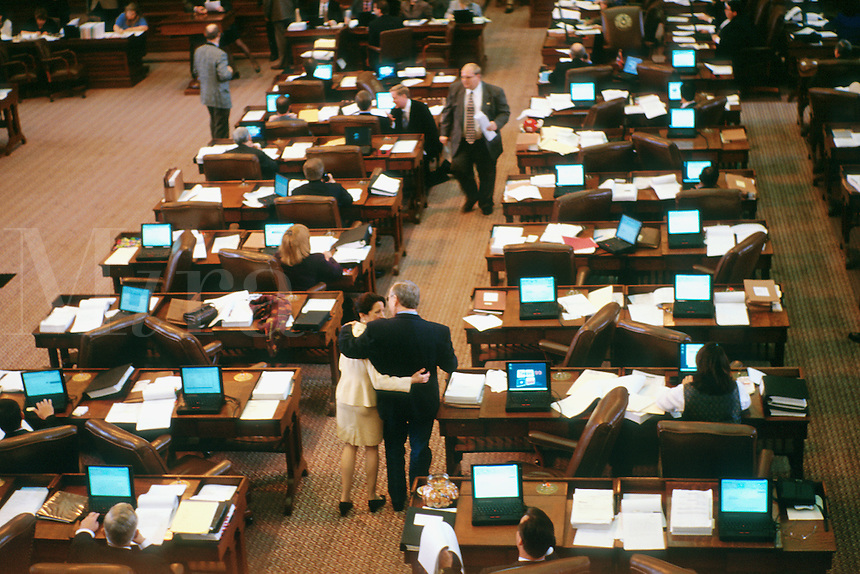 State government. Texas Legislature. 76th Legislative session. Lawmakers walk with arms around each others back. Laptop computers connected by LAN on each legislator's desk allow them to vote electronically. Austin Texas.