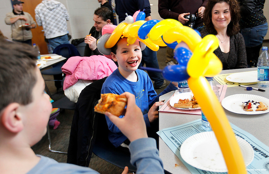 Colby Tomlins, 7, of Hampton, aims his long balloon hat at the camera as his brother, left,  Jake, 9, and mom, Amy, right, look on at the 5th Annual Hampton Rotary Club Pizza Bowl in Hampton, N.H. Sunday, Jan. 30,  2011.  (Portsmouth Herald Photo Cheryl Senter)