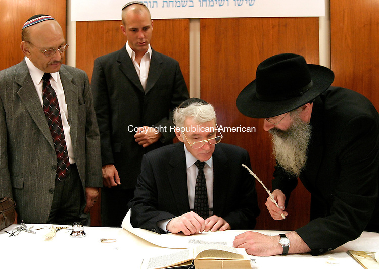 WATERBURY, CT - 10 JULY 2005 -071005JS07--Rabbi Yehuda Clapman, right, of New York City instructs family members of the late David S. Weisman, from left, brother Paul Weisman, son David Weisman and brother Joseph Weisman, on how to fill in the letters of the Torah during a ceremony at the Waterbury branch of Chabad Lubavitch of the Northwest Corner on Sunday. The sefer Torah was commissioned to remember the late David S. Weisman. --Jim Shannon Photo-- David S. Weisman; Rabbi Yehuda Clapman; Paul Weisman; David Weisman, Joseph Weisman are CQ