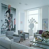 The artwork displayed in this contemporary living room includes a photograph by Candida Höfer hanging on the wall and a large sculpture in front of the floor to ceiling window