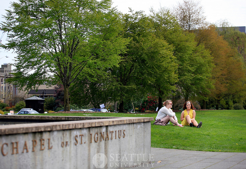 04092012-  Two students sit on the grass next to the Chapel of St. Ignatius while enjoying the warm spring afternoon.