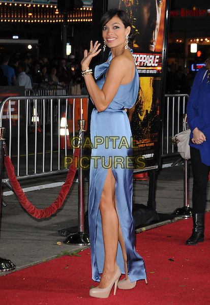 "ROSARIO DAWSON.attends the Twentieth Century Fox's L.A. Premiere of ""Unstoppable"" held at Regency Village Theater in Westwood, California, USA, October 26th 2010..full length dress blue one shoulder silk satin long maxi slit split beige nude shoes clutch bag patent nude platform side thigh leg gold bracelet hand waving .CAP/RKE/DVS.©DVS/RockinExposures/Capital Pictures."