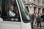 Coach driver waits as wheelchair users chained together block the north side of Oxford Circus in a UK Uncut and Disabled People Against Cuts (DPAC) protest against the Welfare Reform Bill.
