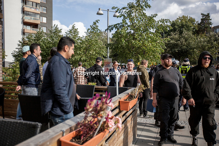 August 25, 2018: Kurdish parishioners react as supporters of the neo Nazi Nordic Resistance Movement NRM (Nordiska motståndsrörelsen) pass by in front of a traditional restaurant in the Solna area after they were escorted by police forces from a demonstration at the Kungsholmstorg square in Stockholm, Sweden. An estimate of 200 supporters of the neo-Nazi organisation held a six-hour rally guarded by a strong police deployment.