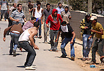 Palestinians hurl rocks at Israeli soldiers during clashes at Qusra village near the West Bank city of Nablus on 16 September 2011. Israeli settlers assaulted the village Friday morning, leading to clashes with Israeli forces injuring 11 Palestinians. After the settlers were removed by Israeli police, Israeli forces raided Qusra village injuring another six villagers with rubber bullets, Palestinian sources said. Photo by Wagdi Eshtayah