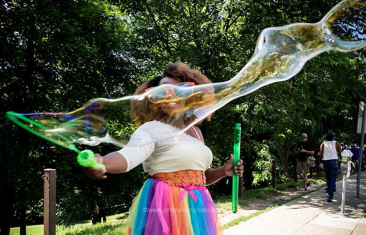 Jenikwa Henry blows bubbles of rainbows at Capital Pride Parade, Washington, DC. <br /> PHOTOS/John Nelson