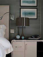 The Art Deco style bedside table displays a model of the Mulsanne while the wall is decoratd with framed drawings of the car