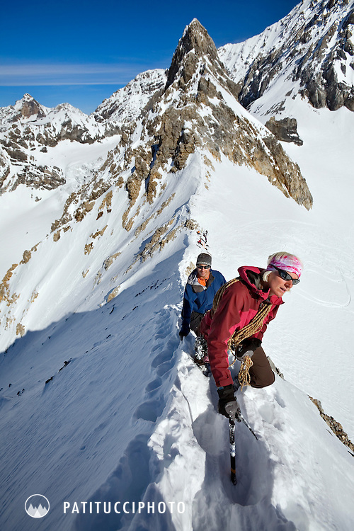 Female mountain guide, Margaret Wheeler, guiding a client on an alpine ridge while on a ski tour of the Ortler area of northern Italy. Margaret is the second American woman to be certified as an international guide through the IFMGA/UIAGM