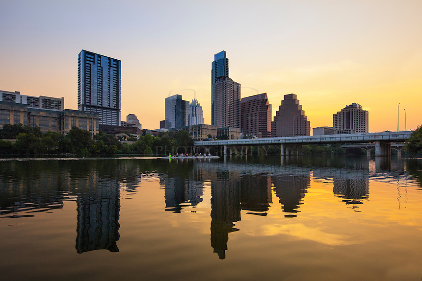 Scullers glide across the orange waters of Lady Bird Lake in the early morning light. In the distance, the highrises of downtown Austin welcome the new day in the capitol city of Texas.