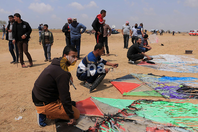 Palestinian protesters prepares kites during clashes with Israeli security forces during tents protest demanding the right to return to their homeland, at the Israel-Gaza border, in Khan Younis in the southern Gaza Strip on April 27, 2018. Photo by Sanad Latefa
