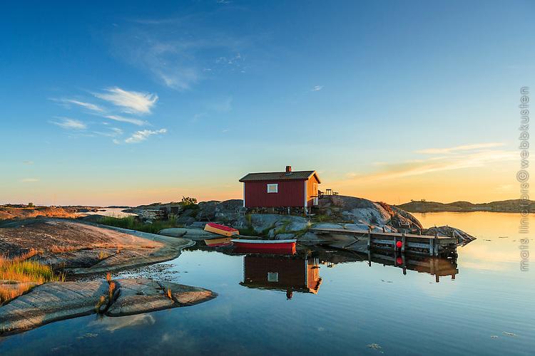 Faluröd fiskebod en stilla och speglblank kväll på Ut-Fredel i Stockholms skärgård. / Shed in the Stockholm archipelago in Sweden.