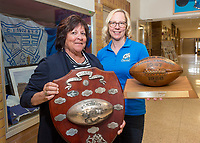 Jayne Collier, a committee helper, left holding a WOSSA Rugby Championship trophy from 1923-1930 while Helen Crick, committee co-chair holds a Sarnia Central Collegiate Centaurs WOSSA  football championship trophy from 1957-1958.