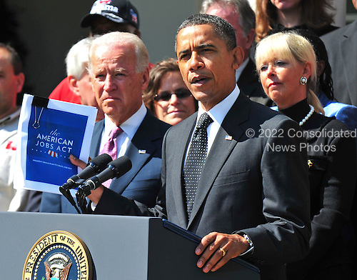 United States President Barack Obama holds up a copy of his jobs creation bill during a statement in the Rose Garden at the White House in Washington on September 12, 2011.  Obama was joined by Vice President Joe Biden and unemployed civil servants who would benefit from the bill. .Credit: Kevin Dietsch / Pool via CNP