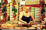 A middle-aged Italian woman cooking different meats and sausages at a market in Little Italy, New York City.