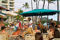 Local musician Kapono playing outside at Duke's Waikiki Beach.