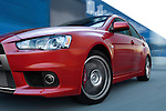 Motion photo of a 2009 Mitsubishi Lancer Evolution MR driving with blue warehouse blurred in background.