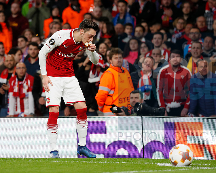 Arsenal's Mesut Ozil picks up and object thrown by the Atletico fans during the Europa League Semi Final 1st Leg, match at the Emirates Stadium, London. Picture date: 26th April 2018. Picture credit should read: David Klein/Sportimage