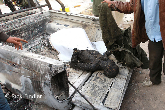 The charred remains of an injured rebel fighter is covered with blankets as it lies on the back of a truck hit by a mortar in the city of Misrata. In February 2011 Libya descended into civil war. Protests in Benghazi escalated into a rebellion against Colonel Muammar Gaddafi and his forces. During the conflict, the coastal city of Misrata saw some of the worst fighting as it fell victim to daily assaults and constant shelling from Gaddafi's army.