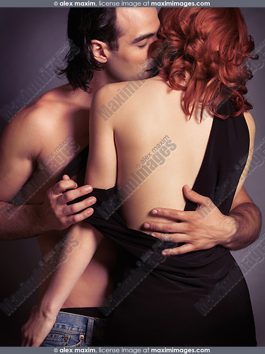 Sensual portrait of a young sexy couple. Man with bare torso kissing a woman in a dress with open low back.