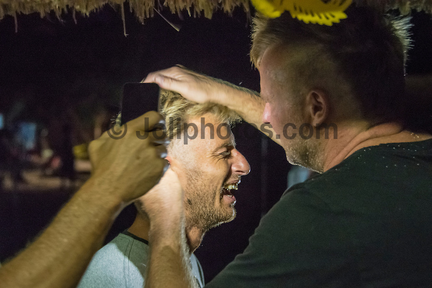 Namotu Island Resort, Nadi, Fiji (Wednesday, June 8 2016): Sebastian Zietz (HAW) being given a haircut by Taj Burrow (AUS). The Fiji Pro, stop No. 5 of 11 on the 2016 WSL Championship Tour, was called off today due to the lack of contestable swell at Cloudbreak. The contest is facing a number of lay days due to the small surf conditions.  The surprise of the day was the return of Joel parkinson (AUS) to the island. His injury wasn't as bad as first thought but he is still out of action for at least 3 weeks.<br /> He'd returned to enjoy the party for Taj Burrow (AUS) which got back into full swing as soon as he landed. Photo: joliphotos.com