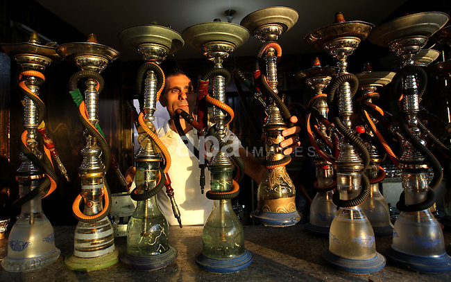 A Palestinian waiter prepares water pipes for customers at a restaurant on Gaza sea beach , in Gaza City on Sept. 28, 2010. One of Gaza hotels is closed on Wednesday for three days by Hamas policemen after allowing for women to smoke water pipes, the hotel owner said, which Hamas has decided on last may to prevent women from smoking water pipes in public places . Photo by Wissam Nassar