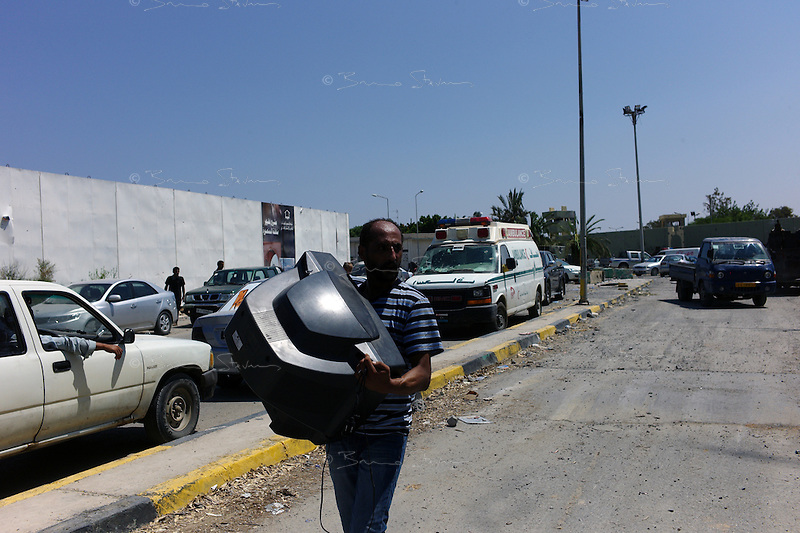 Tripoli, Libya, August 24, 2011.A man exits Khaddafi Bab Azizyah complex carrying a large TV set..
