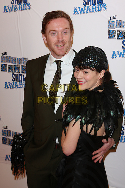 DAMIAN LEWIS & HELEN McCRORY .Attending the South Bank Show Awards at the Dorchester Hotel, Park Lane, London, UK, January 26th 2010..arrivals half length feather cape feathers couple black suit tie arm around married couple husband wife hat .CAP/ROS.©Steve Ross/Capital Pictures.