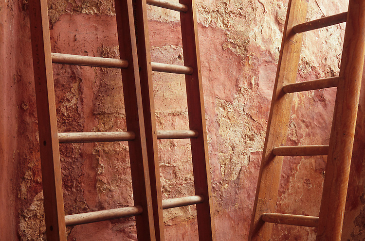 Three wooden ladders leaning on or near rough plaster wall painted pink but flaking badly