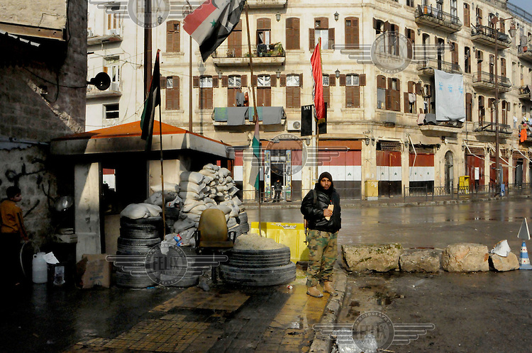 A soldier eats a snack while guarding a checkpoint in government controlled territory in the city centre.