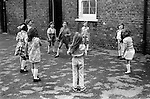 Primary school playground. Girls playing together. South London. 1970s Britain..