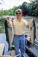 Proud angler with two trophy stripers caught in Illinois River near Vian, Oklahoma