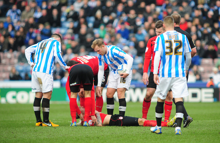 Players from both Huddersfield Town and Cardiff City check on the condition of Cardiff City's Kevin McNaughton who appeared to be knocked out after landing awkwardly following an aerial challenge ..Football - npower Football League Championship - Huddersfield Town v Cardiff City  - Saturday 9th February 2013 - John Smith's Stadium - Huddersfield..